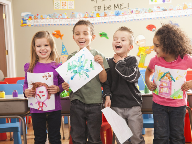 preschool children displaying their artwork