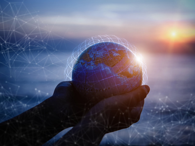 Cupped hands holding animated globe at sunset