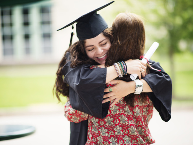 college grad in cap and gown hugging family member