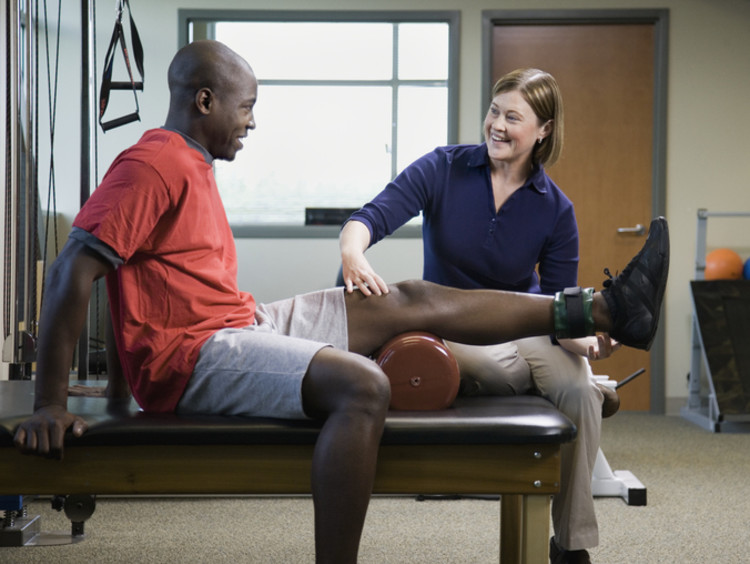 physical therapist working with a patient beside exercise equipment