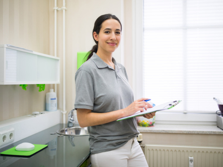 Female nurse in uniform standing in a clinic with clipboard