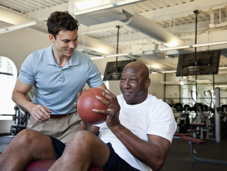 physical therapy assistant helping a patient lift a ball