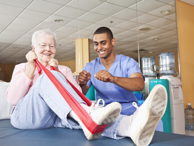 physical therapist helping a patient stretch during a session