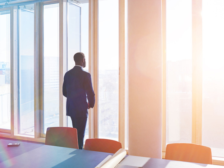 business person staring out of a window contemplating their stewardship