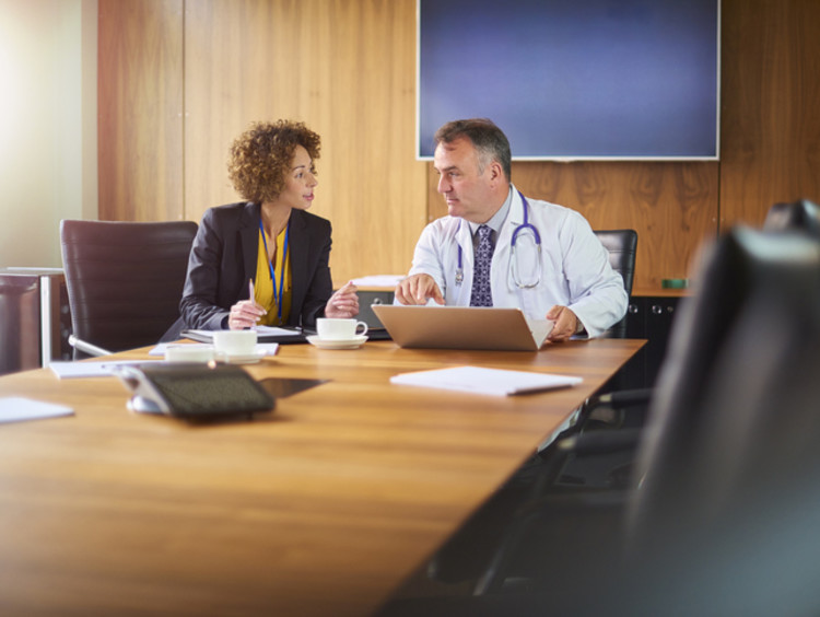 healthcare professional working with a colleague in a meeting room