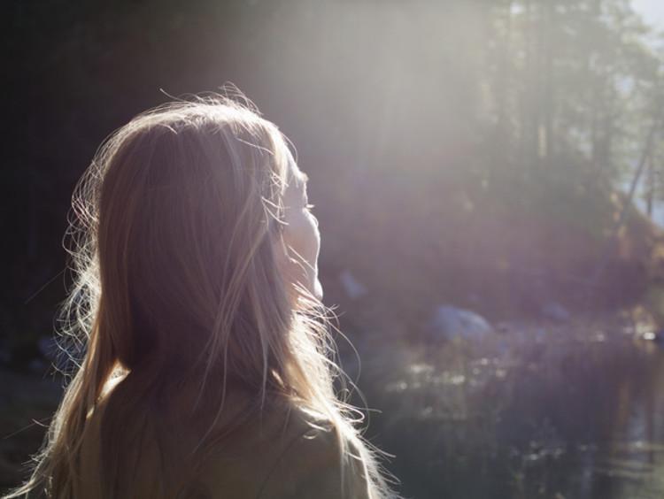 Blonde woman faces sunlight at lake shore