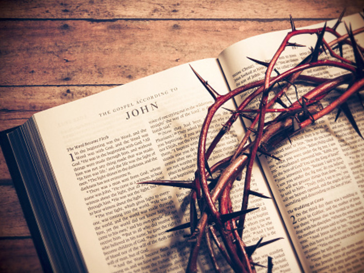 Gospel of John open with crown of thorns on top of it