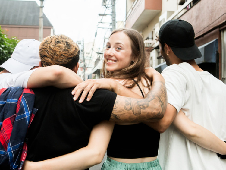 Group of friends walk down a narrow street with arms interlinked