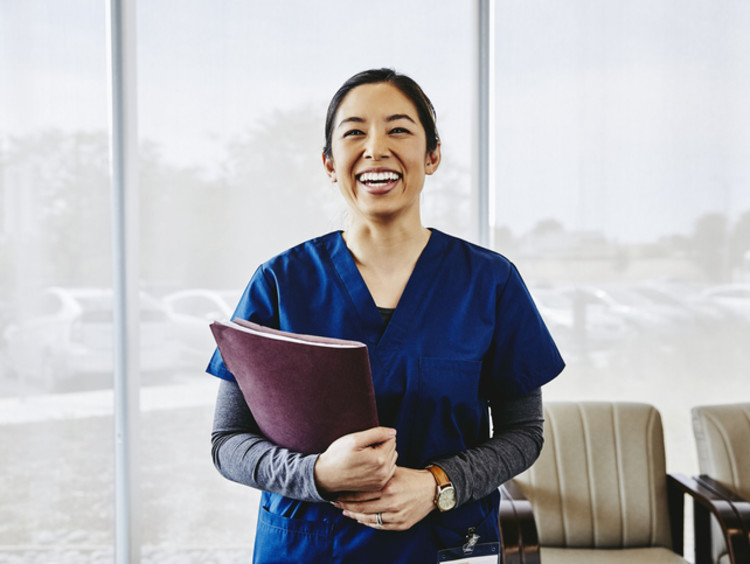 Nurse smiling and holding paperwork in office