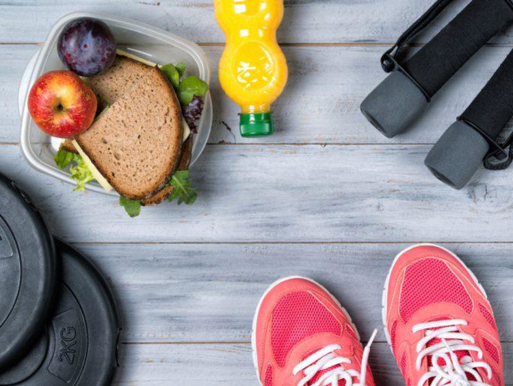 Healthy drink and food in Tupperware next to weights jumprope handles and tennis shoes