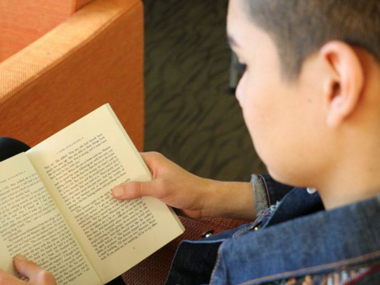 A GCU student reading in the library
