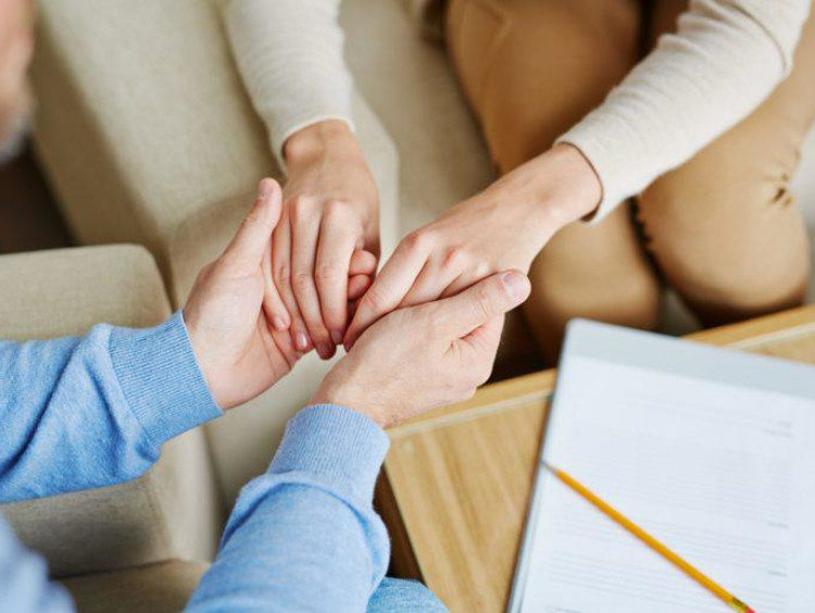 Christian counselor holds client's hands for reassurance