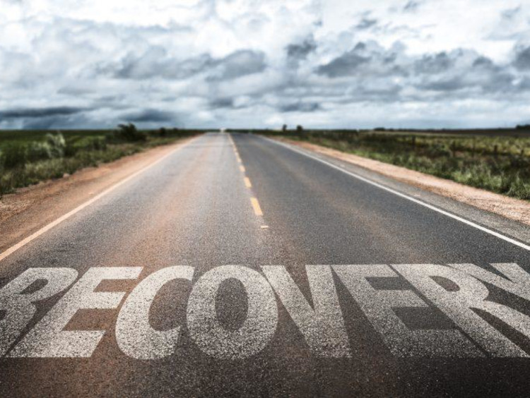 Large letters spell recovery on empty road with a cloudy sky ahead