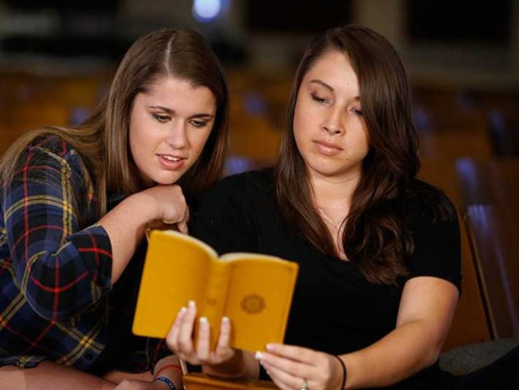 Two young women reading the Bible together