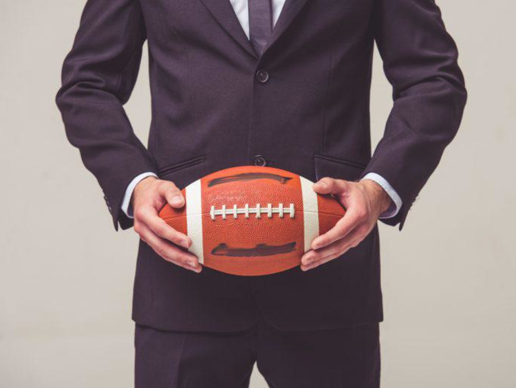 Businessman holds a football