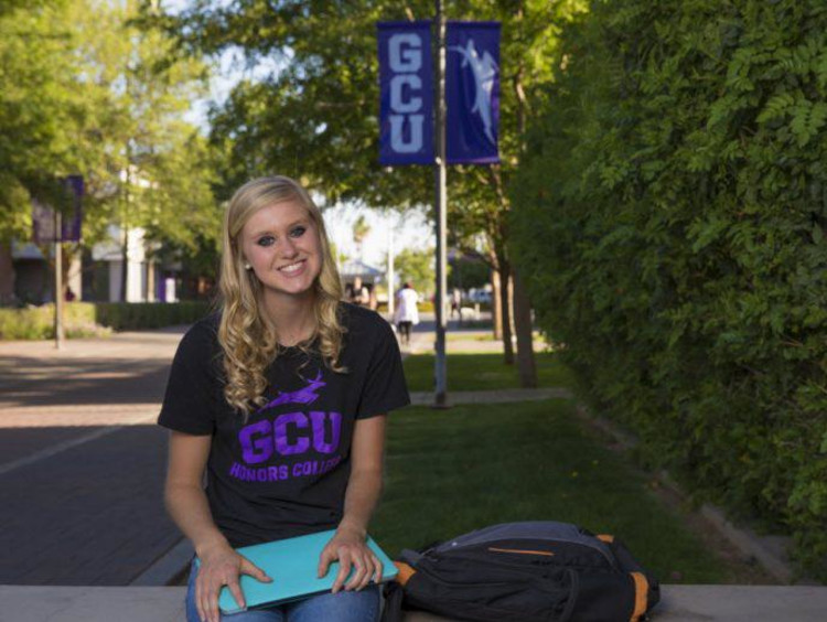 Blonde GCU Honors College student sits outside