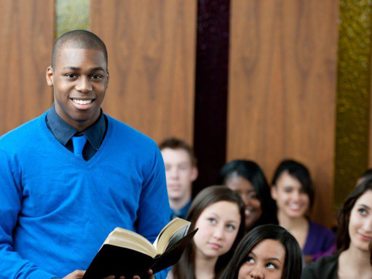 Young male pastor holds bible in full classroom