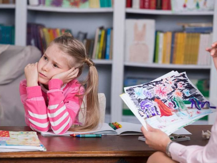 Professional child counselor looks at little girl's drawing while girl in pink looks distressed