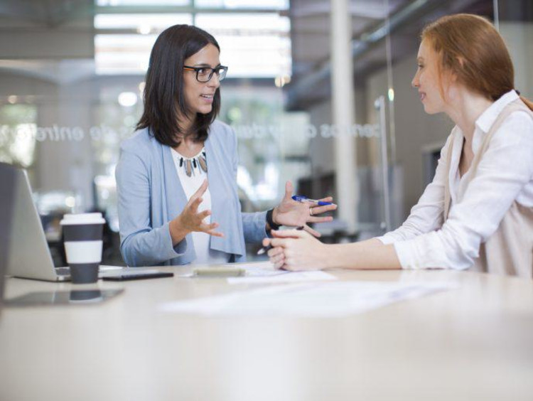 Life coach sits with a client in conference room with glass walls