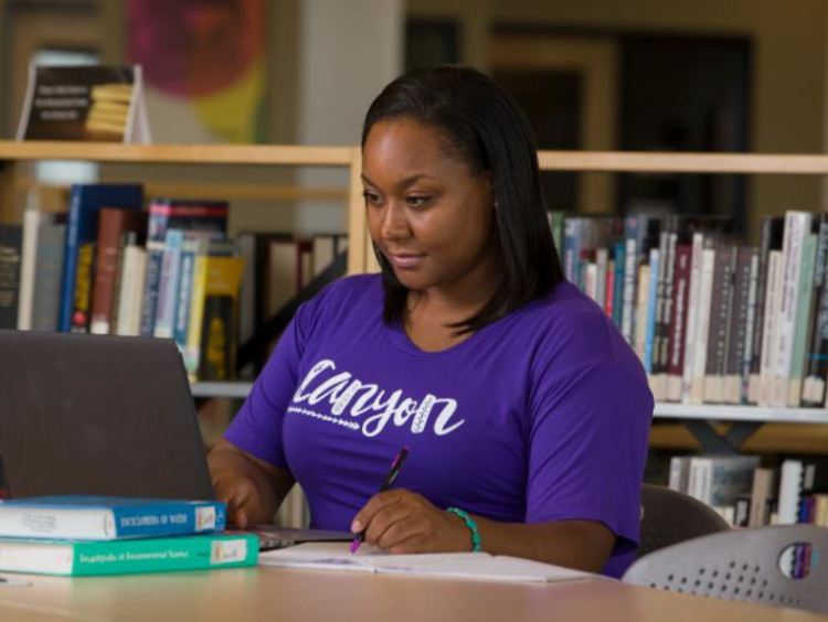 GCU Student in library working on laptop
