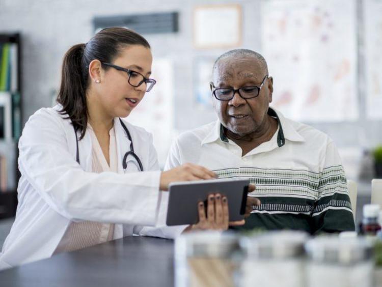 Nurse with older man reading