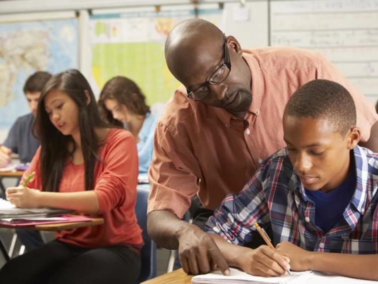 Teacher helps student at their desk
