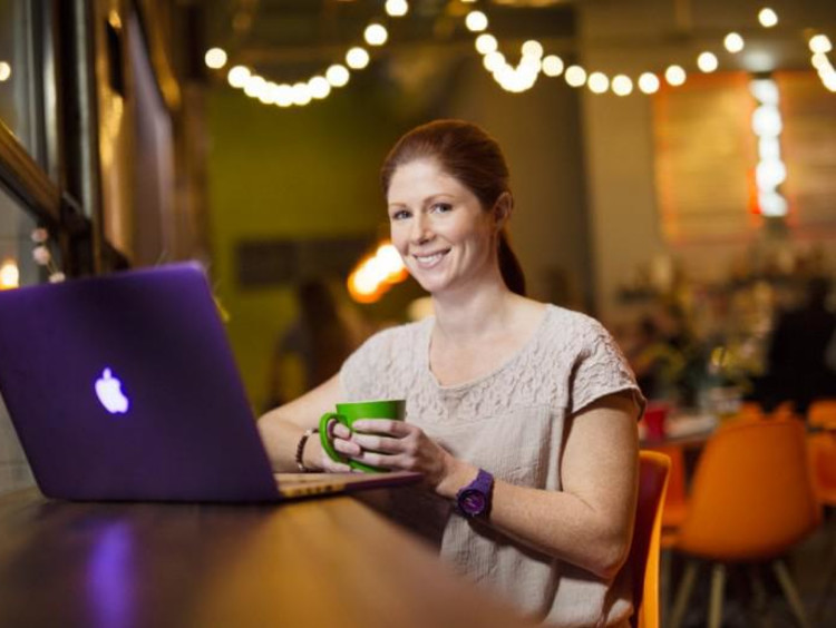 Girl smiles while using her laptop in a trendy coffeeshop