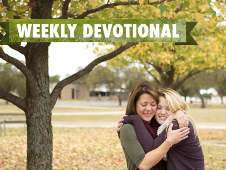 Two girls hugging under the Weekly Devotional banner