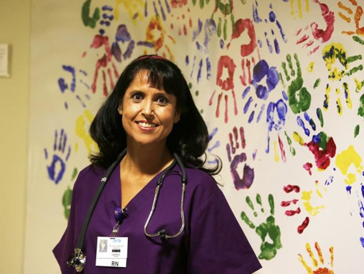 Nurse next to wall full of colorful handprints