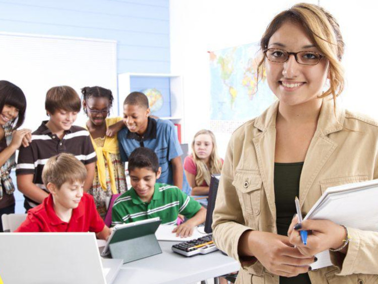 teacher smiling and students working in the background