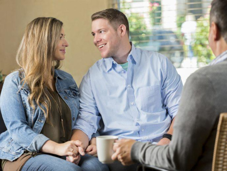 Marriage therapist with a cup of coffee observes couple looking lovingly at each other