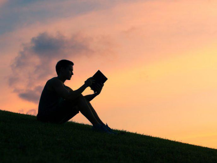 person reading at sunset