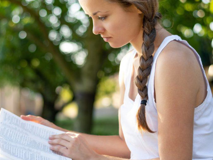 woman reading her bible outside