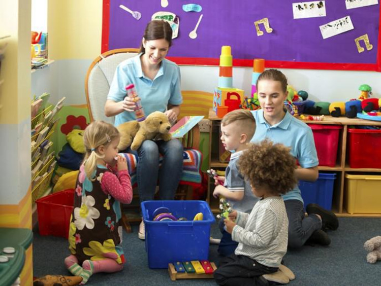Two nursery workers play with kids in colorful nursery