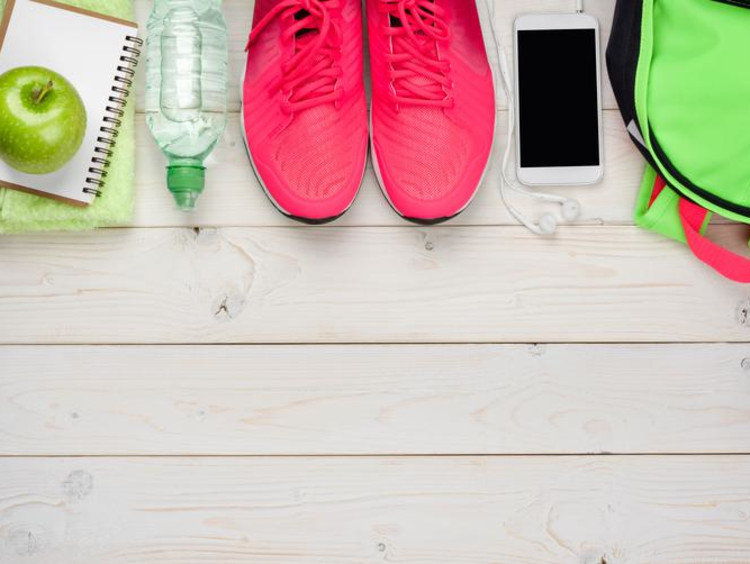 Sports gym bag contents lined up with bright pink athletic shoes in middle