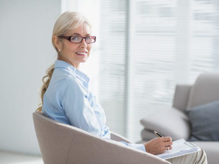 Cognitive psychologist turns around in chair with glass window showing high rise view outdoors