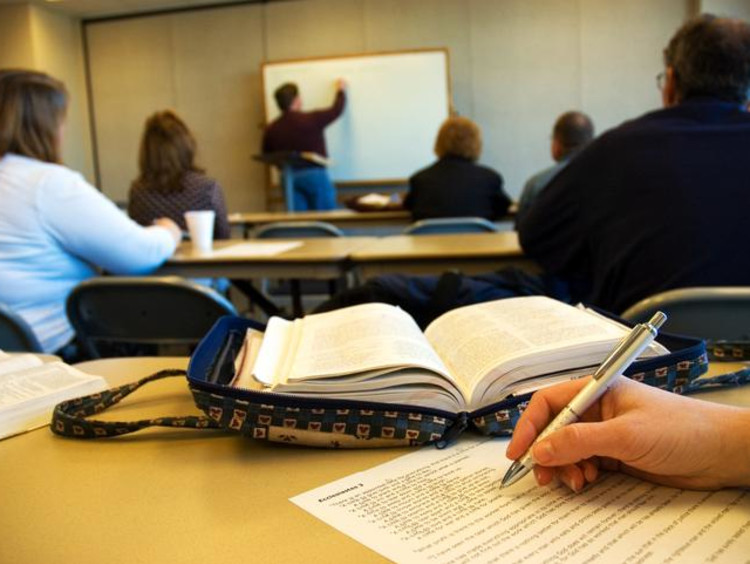 Students in the classroom writing an assignment