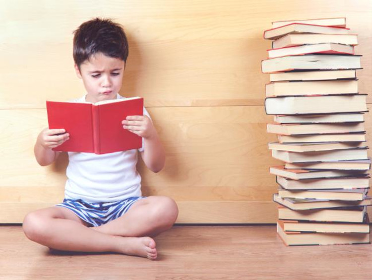 Little boy sitting next to tall stack of books
