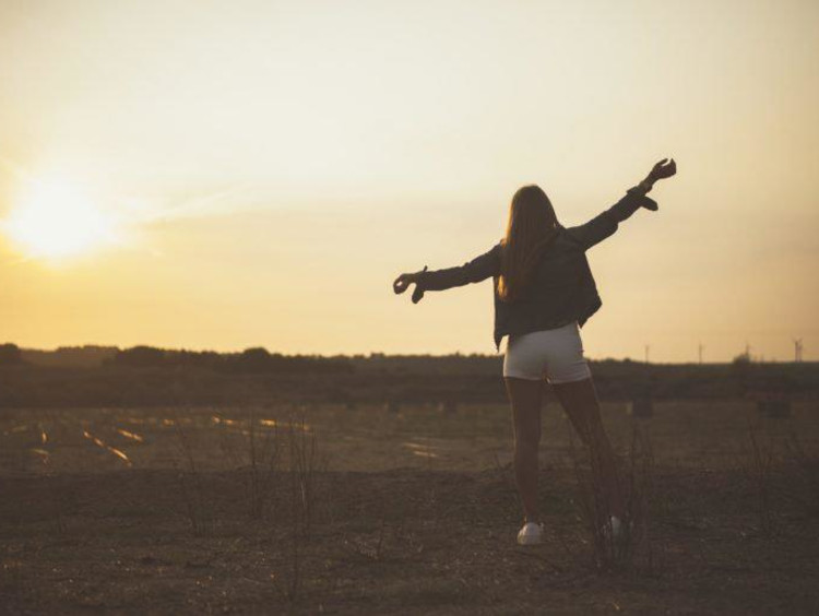 girl standing in a field at sunset with her arms out