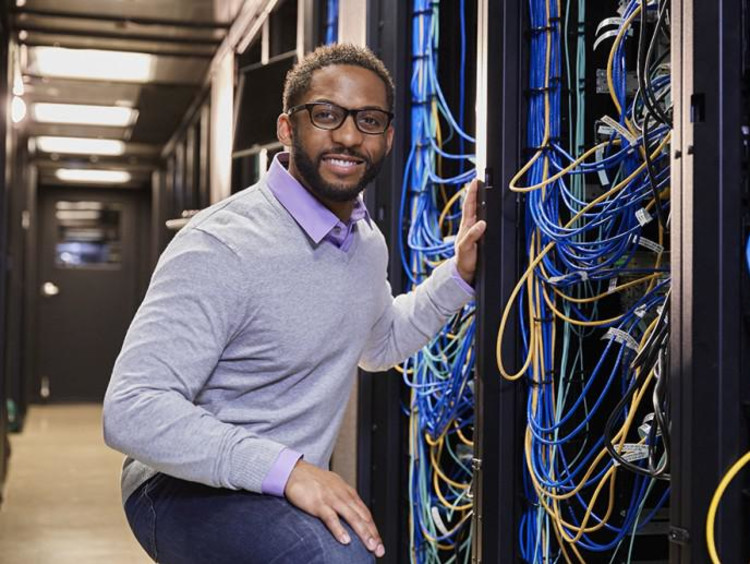 Male African-american IT worker with glasses in light purple sweater kneeling near a server tower