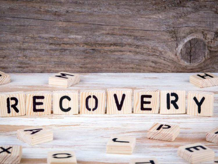 Letters on upright wood squares spell out recovery