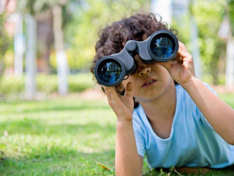 kid looking through binoculars
