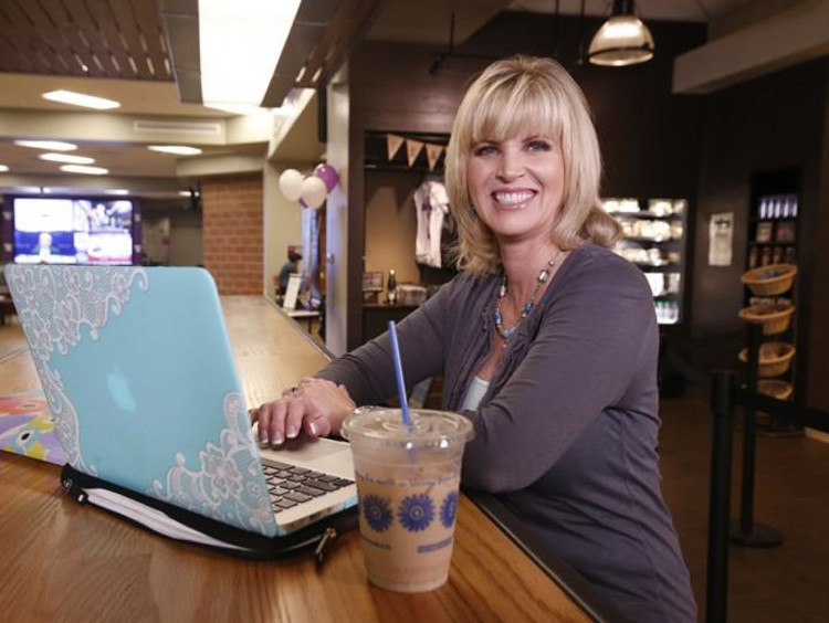 Middle-aged blonde sits a high rise table in a coffee shop