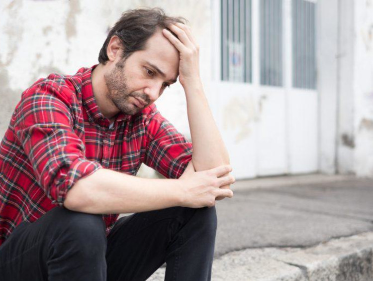 Young male looks depressed sitting at the curb