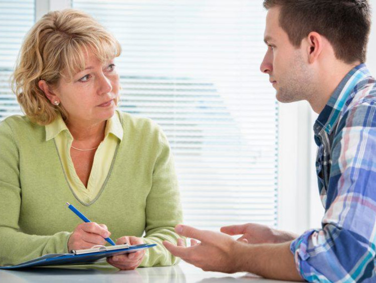 Blonde mental health specialist takes notes of a younger male talking to her