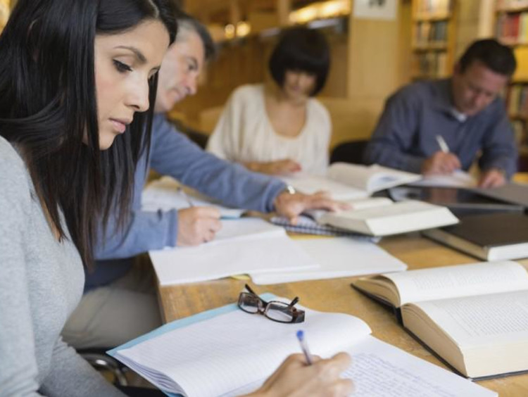 Group of adult students do course work in a library