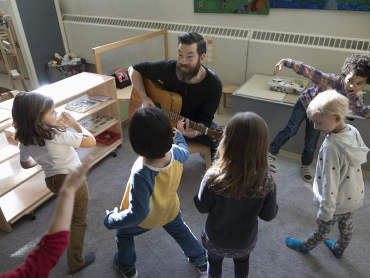 Man playing guitar with little kids around him