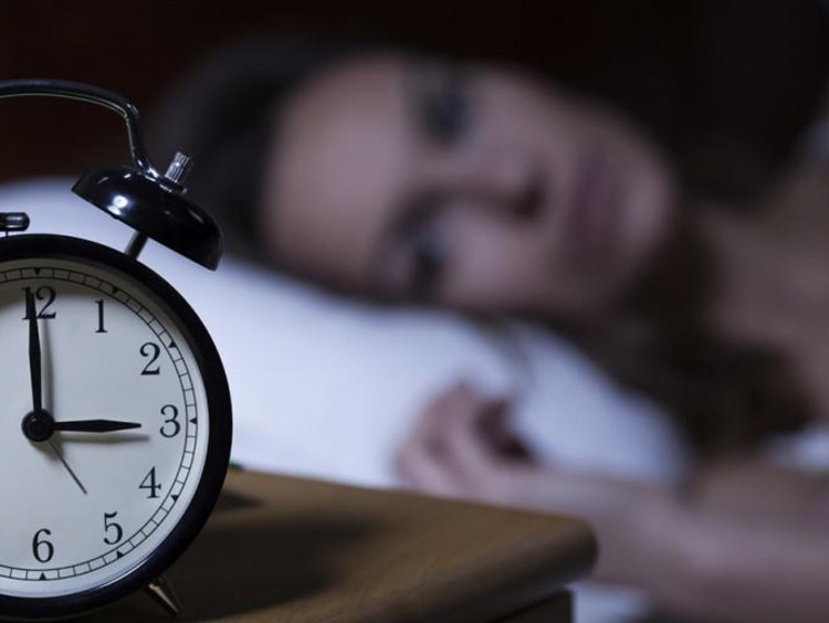 woman laying in bed looking at alarm clock