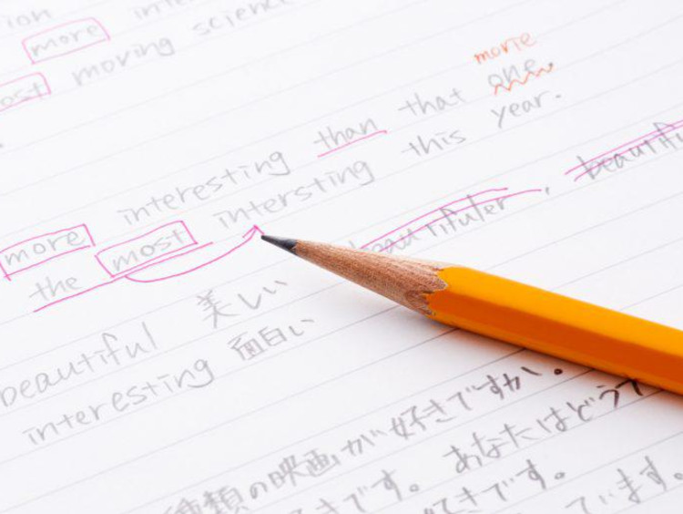 Pencil sits on top of ESL writing assignment with edits