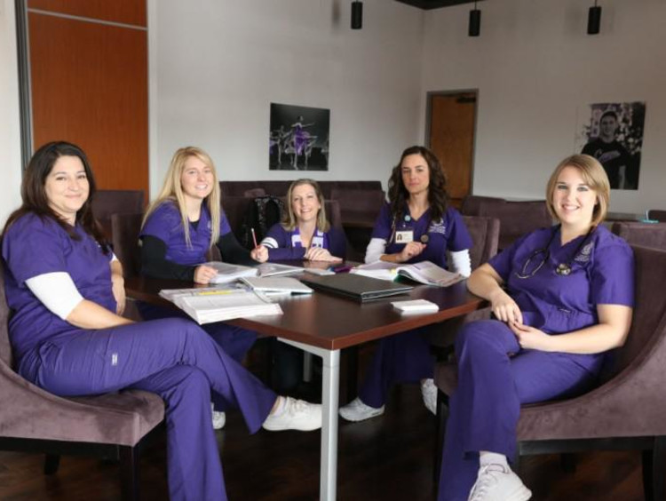 five nurses sitting around a table working